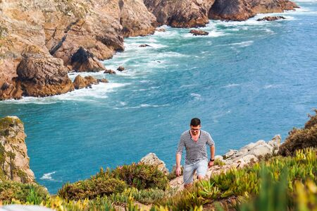 Stylish, young man standing at the very edge of the rock and staring into the distance the place where the earth ends and the sea begins, Cabo da Roca Cape Roca , Sintra, Portugal