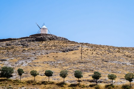 Beautiful and old windmills painted in white, standing in the hills against the blue sky