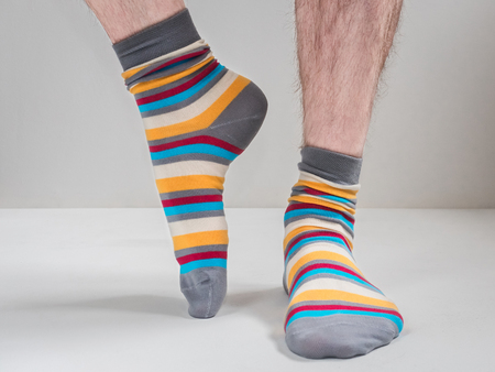 Men's feet in funny, colorful socks on a white background