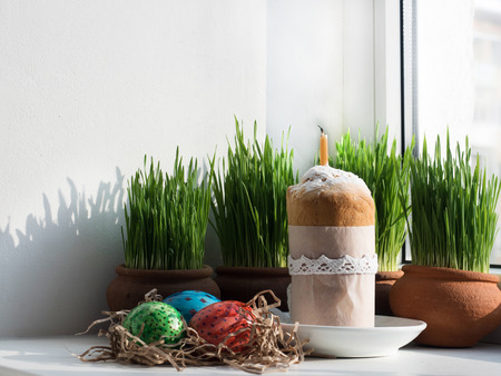 Fragrant cupcake on a background of fresh, green grass in pots. Preparing for Easter