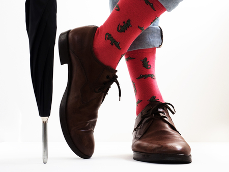 Men's legs in bright, funny socks and stylish shoes near the umbrella Archivio Fotografico