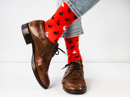 Bright, funny socks, vintage, brown shoes and mens feet on a white background. Fashion, style, beauty