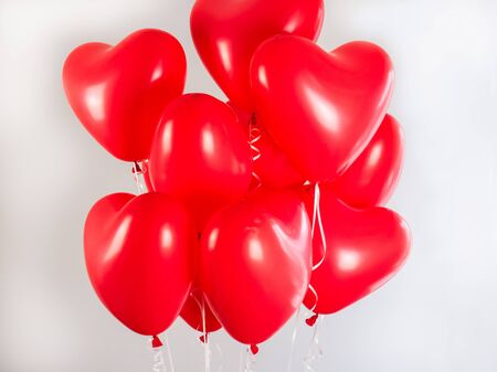 Red balloons in the shape of a heart filled with helium, on a white background. Festive event