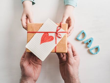 Beautiful box with a gift, a card with a heart and a word dad in the hands of a youngest daughter on a white background. The view from the top. Congratulations for your beloved daddy