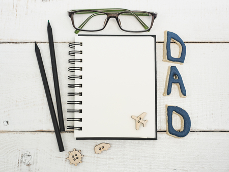 Blank note pad for fathers congratulations, a word from the letters DAD, glasses, pencil, pen on a beautiful, white table. Top view of a close-up. Preparation for the holiday Stock Photo