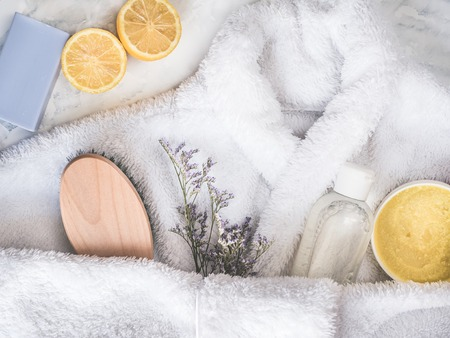 White bathrobe, aroma-oil, cream-scrub, shampoo, piece of lavender soap, slice of lemon and a beautiful, blooming flower. Preparing for the Spa Treatment. Concept of beauty and health