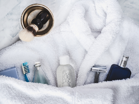 White bathrobe, shaving accessories, lotion aftershave, shampoo, bottle of perfume and piece of lavender soap. Preparing for the Spa Treatment. Concept of beauty and health