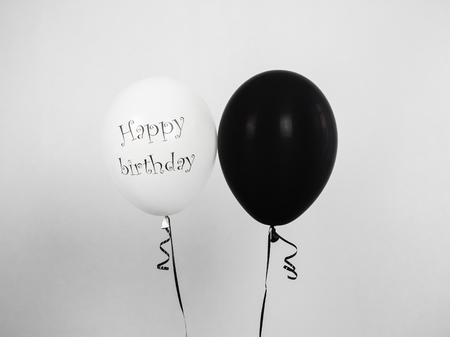 Black and white balloons with birthday greetings, on white isolated background. Preparation for the festive event. Congratulations for colleagues, relatives, friends and loved ones