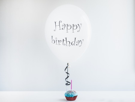 White, helium balloon with birthday greetings and cupcake with candle. White, isolated background. Preparation for the festive event. Congratulations for colleagues, relatives, friends and loved ones Stock Photo