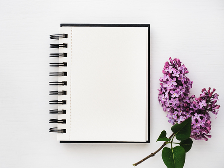 Notepad, blank page for Your inscriptionon on the background of blossoming flowers lilac. Top view, close-up. Congratulations for relatives and loved ones. Concept of a happy family