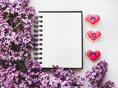 Heart-shaped cookie with the word MOM, covered with bright glaze, notepad with a blank page for Your inscription on the background lilac flowers. Top view, close-up. Congratulations for loved ones