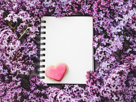 Heart-shaped cookie, covered with bright glaze, notepad with a blank page for Your inscription on the background flowers lilac. Top view, close-up. Congratulations for relatives and loved ones