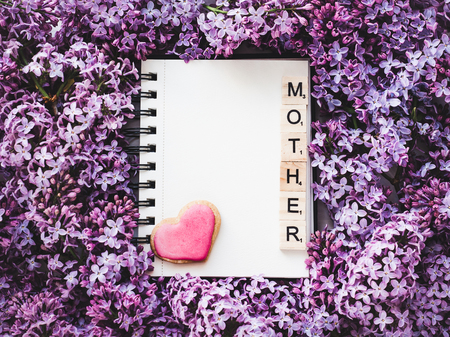 Heart-shaped cookie, covered with bright glaze, word MOTHER, notepad with a blank page for Your inscription on the background flowers. Top view, close-up. Congratulations for relatives, loved ones Stock Photo