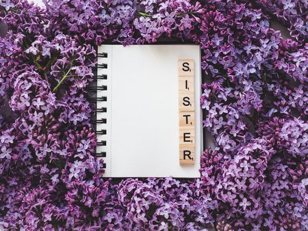 Notepad with the word SISTER and a blank page for Your inscriptionon on the background of blossoming flowers. Top view,close-up. Congratulations for relatives and loved ones. Concept of a happy family Stock Photo