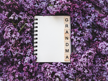 Notepad with the word GRANDMA and a blank page for Your inscriptionon on the background of blossoming flowers. Top view,close-up. Congratulations for relatives and loved ones.Concept of a happy family