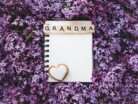 Heart-shaped cookie, covered with bright glaze, word GRANDMA, notepad with a blank page for Your inscription on the background flowers. Top view, close-up. Congratulations for relatives, loved ones