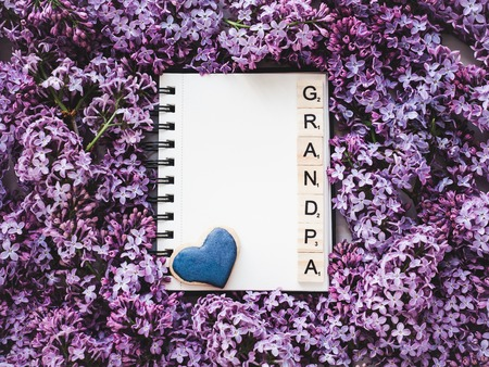 Heart-shaped cookie, covered with bright glaze, word GRANDPA, notepad with a blank page for Your inscription on the background flowers. Top view, close-up. Congratulations for relatives, loved ones Stock Photo