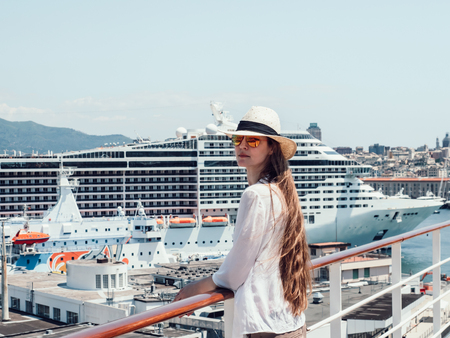 Woman standing on the deck of a cruise ship Stock Photo