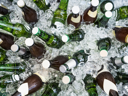 Cubes of ice and colorful bottles with cold beer and drinks. Top view, close-up. Preparation for the festive event