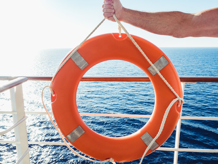 Male hand holding a bright, orange lifebuoy on the top deck of a cruise liner against a background of sea waves, morning sun and clear, blue sky. Concept of safety, care and assistance