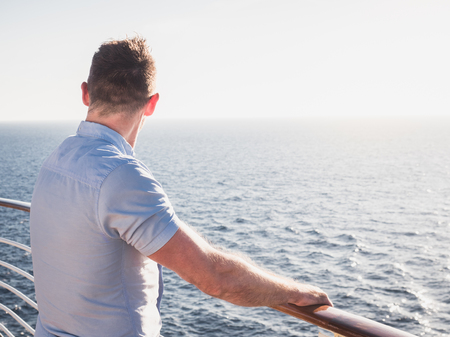 Attractive man in sunglasses on the top deck of a cruise ship looking out into the distance against the background of a sunset. Concept of sea travel and recreation