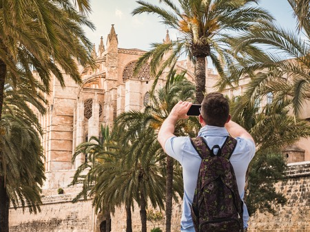 Stylish, happy man with a smartphone on the background of a river, palm trees and historic, famous building in a summer, sunny day