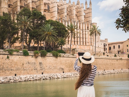 Stylish, happy woman with a smartphone on the background of a river, palm trees and historic, famous building in a summer, sunny day Stock Photo