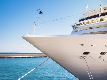 Seascape. Ship on the background of a coastline and a clear blue sky