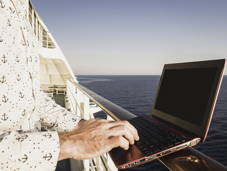 Stylish, attractive man with laptop on the deck of a cruise ship on a background of sea waves and blue sky