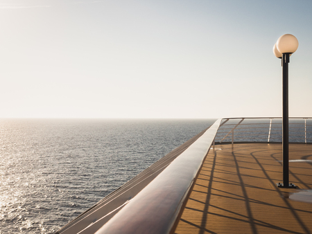 Empty sea deck of a cruise ship at dawn in the open sea against a blue sky and a bright sun