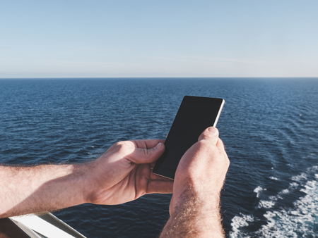 Mens hands holding a mobile phone on the deck of a cruise ship against the background of sea waves