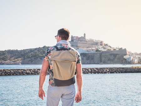 Attractive, stylish guy with a backpack, standing with his back on the background of the sea bay with the ships on a sunny, clear day