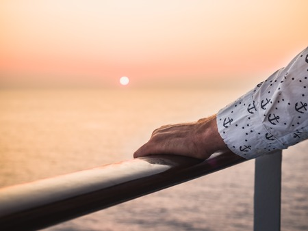 Mens hands on the railing of a cruise ship against the backdrop of sea waves and a fantastic sunset. Sea cruises and rest