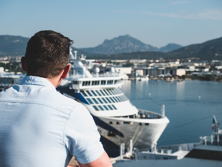 Attractive man on the top deck of a cruise ship on the background of the coastline, city buildings and ships. Concept of sea travel and recreation