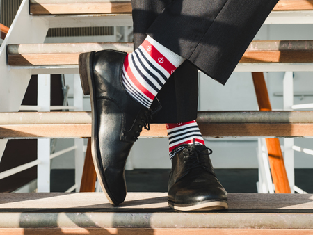 Man in stylish, black shoes, dark pants and funny, bright, striped socks with a pattern on the deck of a cruise ship. Lifestyle, fashion, fun