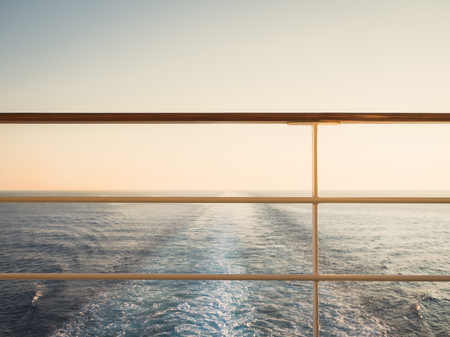 Railing on the empty, open deck of a cruise liner against the background of sea waves. Sunset photo