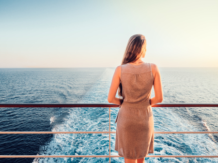 Stylish, young woman on an empty deck of a cruise ship against a background of sea waves, blue sky and sunset