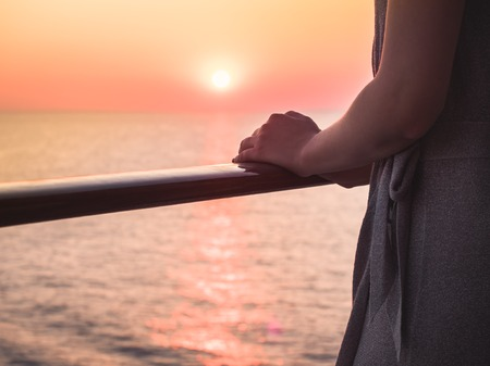 Female hands on the railing of a cruise ship against the backdrop of sea waves and a fantastic sunset. Sea cruises and rest
