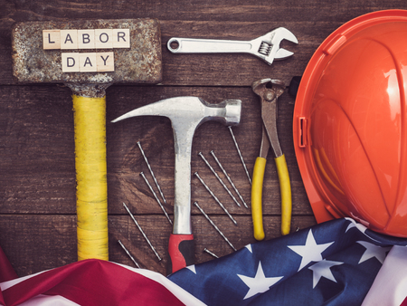 Old tools and wooden letters with the inscription LABOR DAY on the background of a vintage, wooden, brown surface. Top view, close-up. Preparing for the celebration of Labor Day