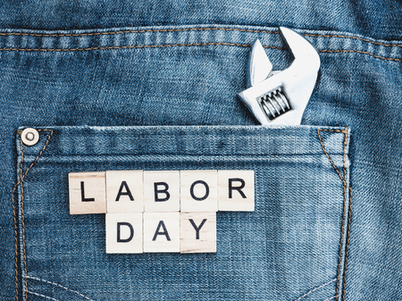 Tools and wooden letters with the inscription LABOR DAY on the background of a blue jeans pocket. Top view, close-up. Preparation for the celebration of Labor Day Stock Photo
