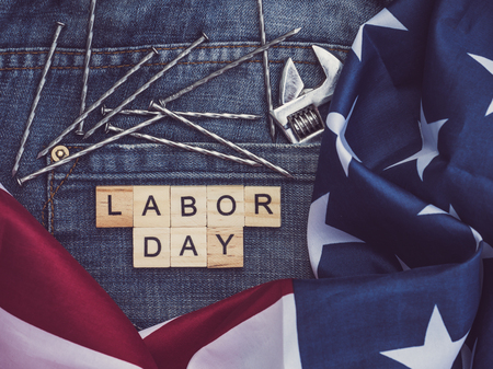 USA flag, tools, and wooden letters with the inscription LABOR DAY on the background of a blue jeans pocket. Top view, close-up. Preparation for the celebration of Labor Day Stock Photo
