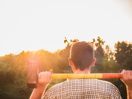 Attractive guy in work clothes, holding a sledgehammer on his shoulders and looking into the distance against the background of trees, blue sky and sunset. View from the back. Concept of Labor Day
