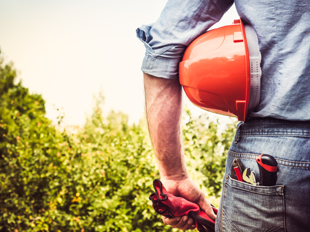 Man in work clothes with tools, standing on a background of trees and blue sky. View from the back, close-up. Concept of work and employment Stock Photo