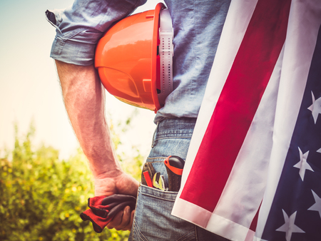 Attractive man in work clothes, holding tools and a US flag in his hands and looking into the distance against the background of trees, blue sky and sunset. View from the back. Labour Day Concept
