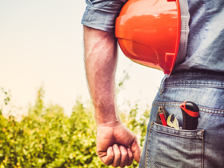 Worker with tools and an orange helmet standing against a background of green trees and blue sky. Rear view, close-up. Concept of work and employment