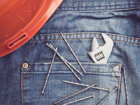 Old tools on the background of a blue jeans pocket. Top view, close-up. Preparation for the celebration of Labor Day. The concept of labor and employment