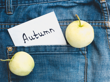 Two ripe apples and a note with the inscription AUTUMN on the background of blue, stylish jeans. Top view, close-up. Seasonality Conception Stock Photo