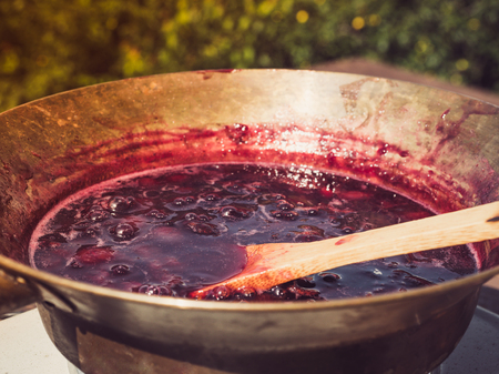 Old, copper pan, wooden spoon and plum jam
