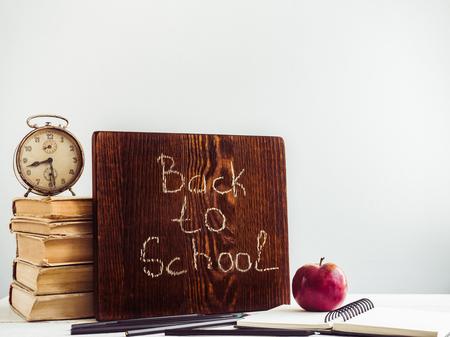 Vintage books, old clock, pencils, red apple and blackboard