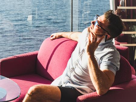 Stylish man with a phone in a red chair on a cruise ship